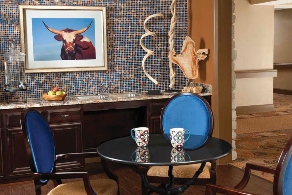 A coffee table with several chairs and a photo of a cow in the background at Isle at Cedar Ridge in Cedar Park, Texas