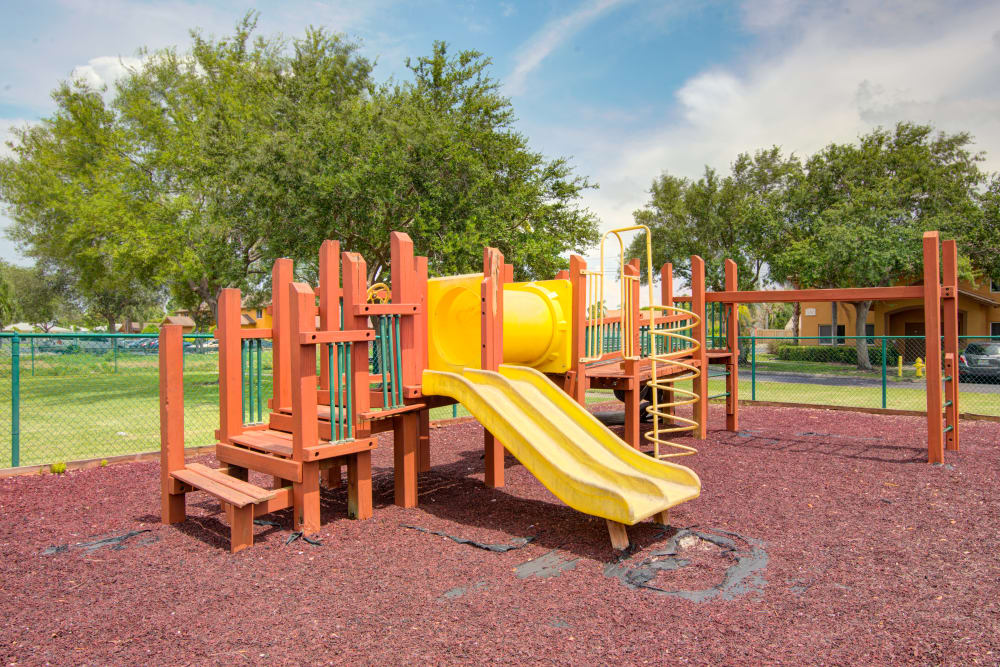 A playground with a slide and monkey bars at Running Brook Apartments in Miami, Florida