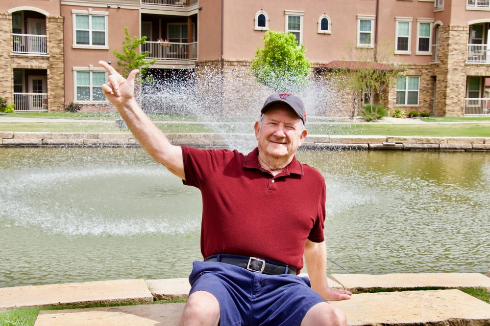 A man waiving while sitting on the fountain at Isle at Raider Ranch in Lubbock, Texas