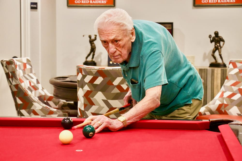 A man playing pool on a table with red felt at Isle at Raider Ranch in Lubbock, Texas