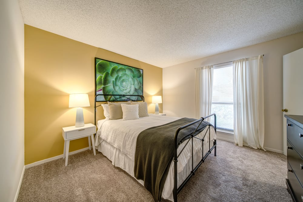 A bedroom with plush carpeting and a large window at Waterview Apartment Homes in Memphis, Tennessee