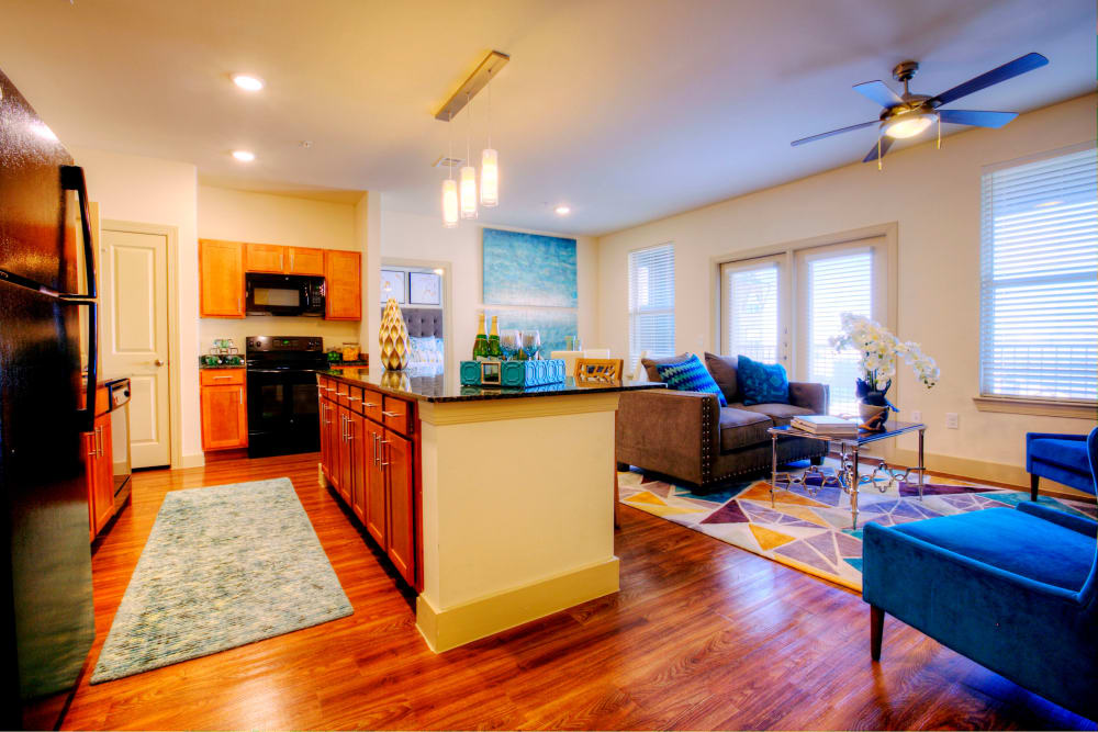 A view of the living room and kitchen of an apartment at Watercrest at Kingwood in Kingwood, Texas