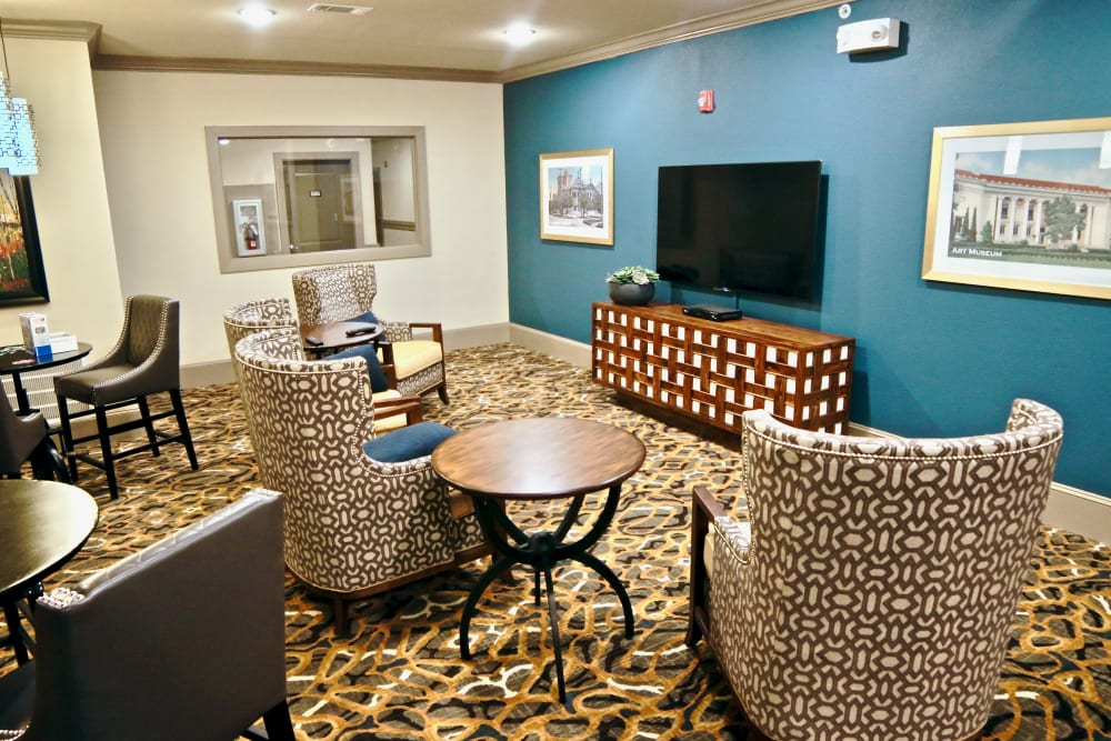 A tv and lounge area with comfy seating and an end table at Watercrest at Shadow Creek Ranch in Pearland, Texas