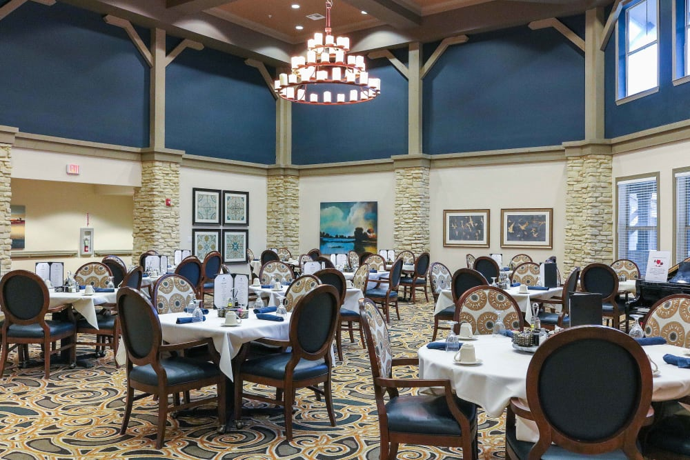 The dining room with decorated tables and fancy chandelier at Landing at Watercrest Shadow Creek Ranch in Pearland, Texas
