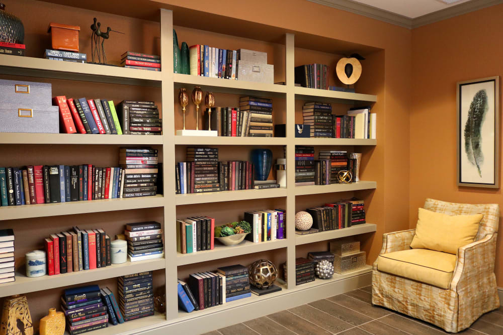 A full bookshelf with a comfy yellow chair at Landing at Watercrest Shadow Creek Ranch in Pearland, Texas