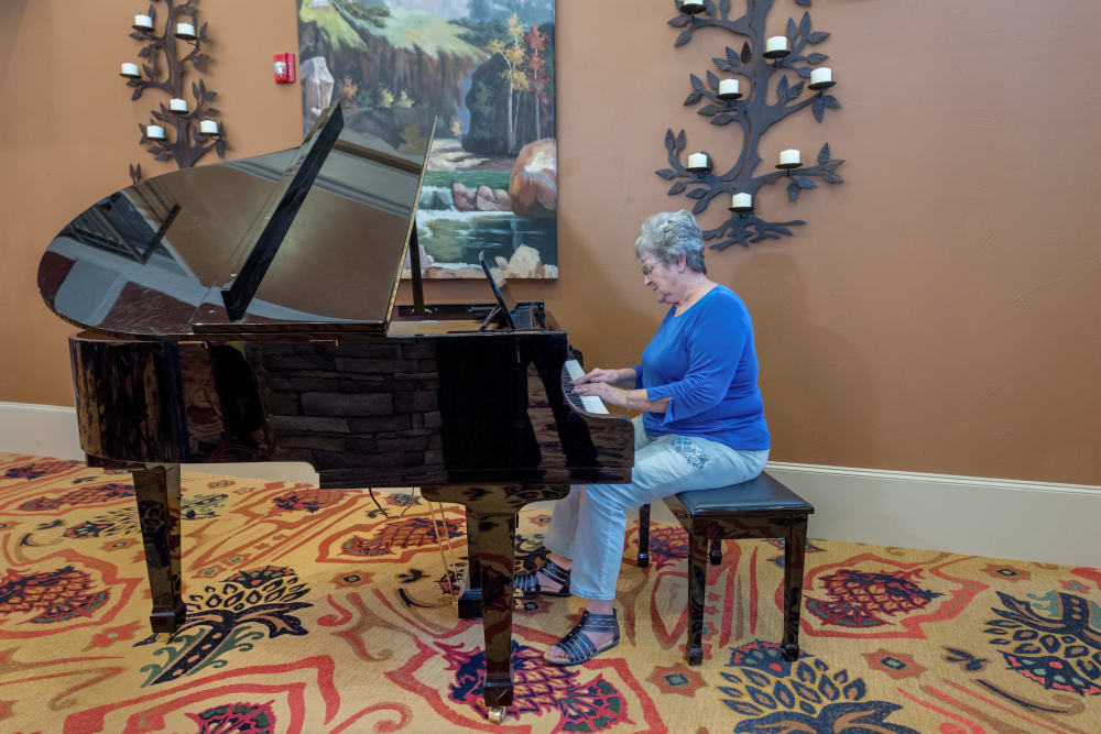 A resident playing on the piano at Watercrest at Bryan in Bryan, Texas