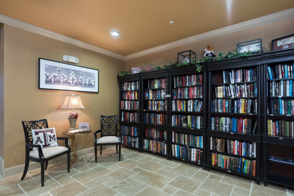 A full book shelf with two chairs and a coffee table at Watercrest at Bryan in Bryan, Texas