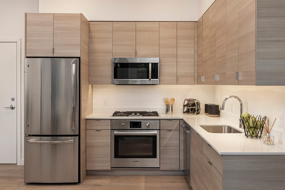 Modern kitchen with energy efficient, stainless-steel appliances in a model home at TwentyTwenty Apartments in Portland, Oregon
