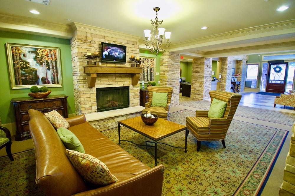 A large room with television, a couch, a chair, and a coffee table at Isle at Watercrest Bryan in Bryan, Texas