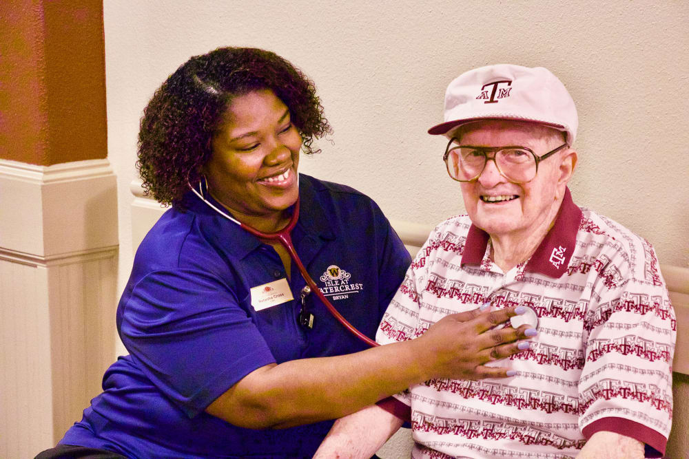 A caretaker with a resident at Isle at Watercrest Bryan in Bryan, Texas