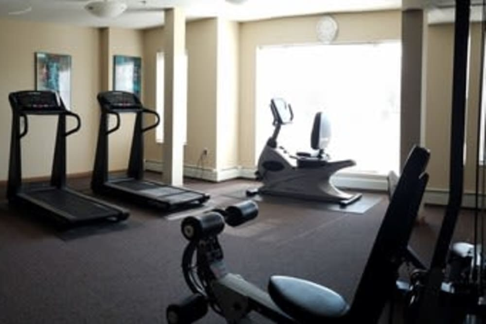 Fitness center with individual workout stations at Parkway Gardens Senior Apartment Community in Saint Paul, Minnesota
