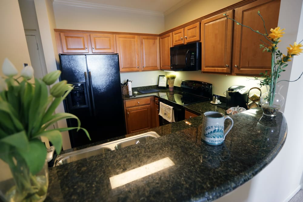 An apartment kitchen with granite counter tops at The Chamberlin in Hampton, Virginia