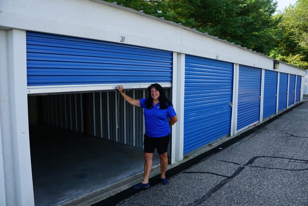 An outdoor storage unit with an employee in front of it at Store It All Self Storage - Lakeway in Lakeway, Texas