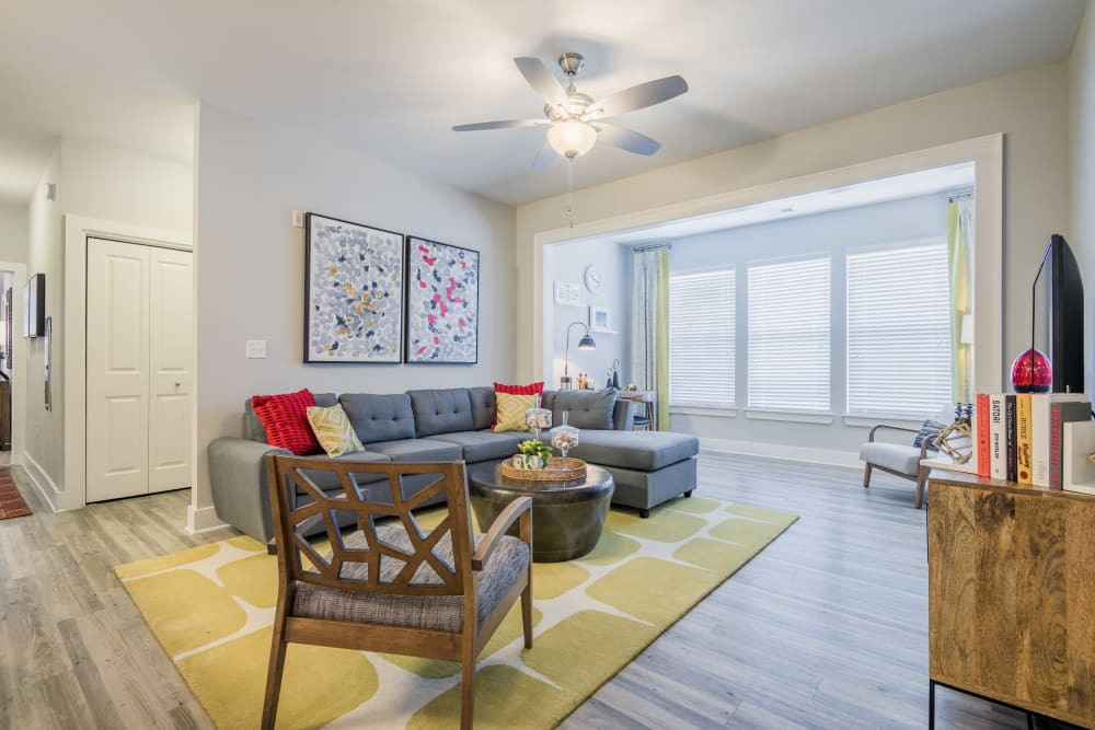 Model living room with wood-style flooring at The Veranda at Market Common in Myrtle Beach, South Carolina