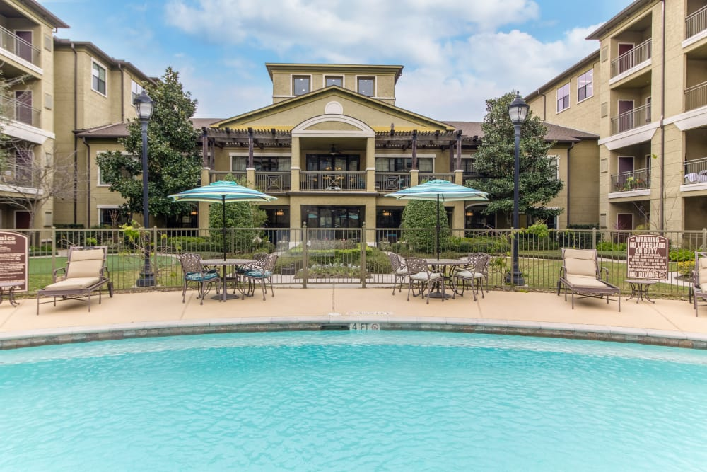 Exterior view of our luxurious senior living community from the pool in Spring.
