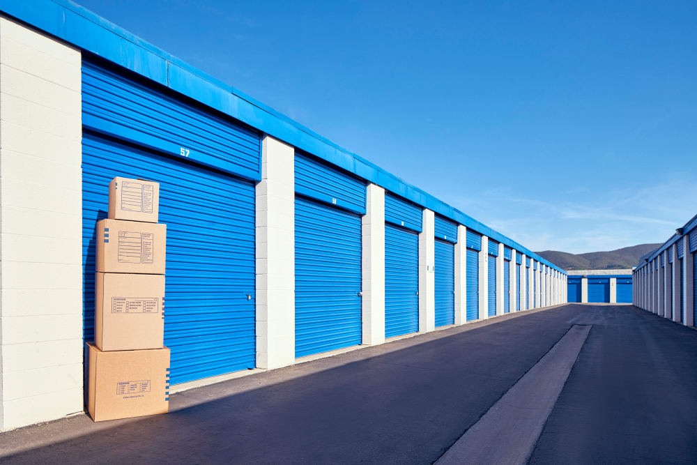 Storage boxes in front of outdoor storage units at Stor'em Self Storage in San Marcos, California