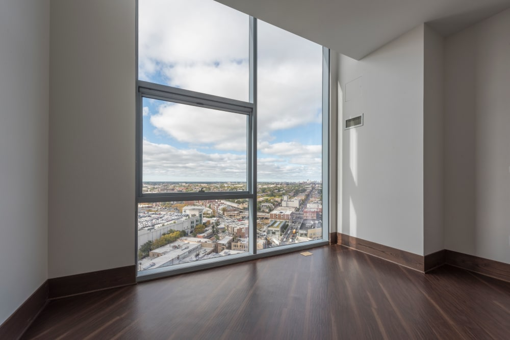 Spacious room with a large window for natural lighting at The Residences at NEWCITY in Chicago, Illinois