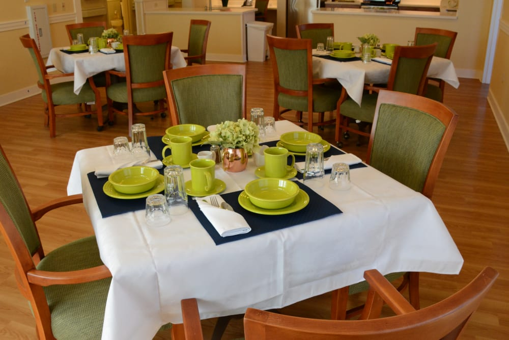 Dining room table with plates and silverware at Artis Senior Living of Commack in Commack, New York