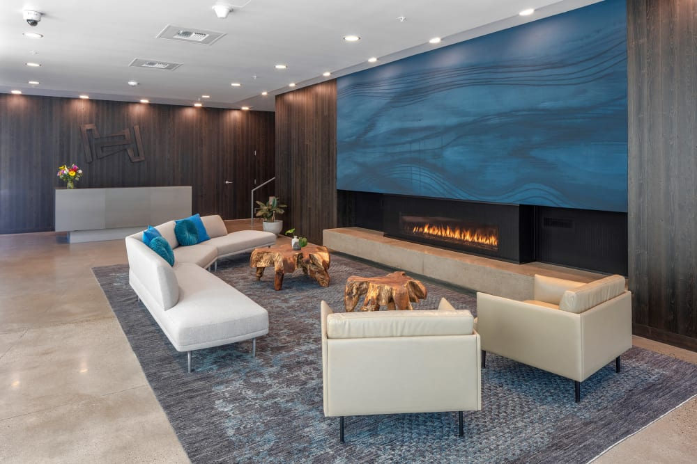 Contemporary furnishings in front of the fireplace in the lobby at TwentyTwenty Apartments in Portland, Oregon