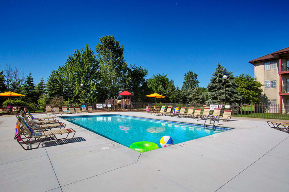 Swimming pool with lounge chairs and umbrellas at Stone Crest in Mt Pleasant, Michigan