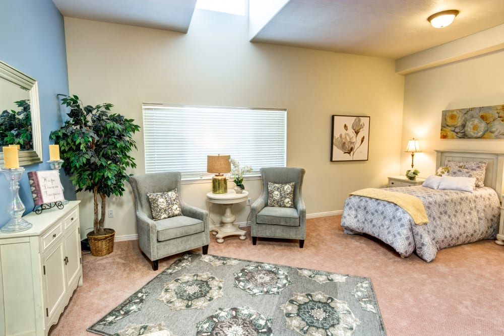 Studio apartment model unit with bed and seating area at The Wentworth at Coventry in Salt Lake City, Utah