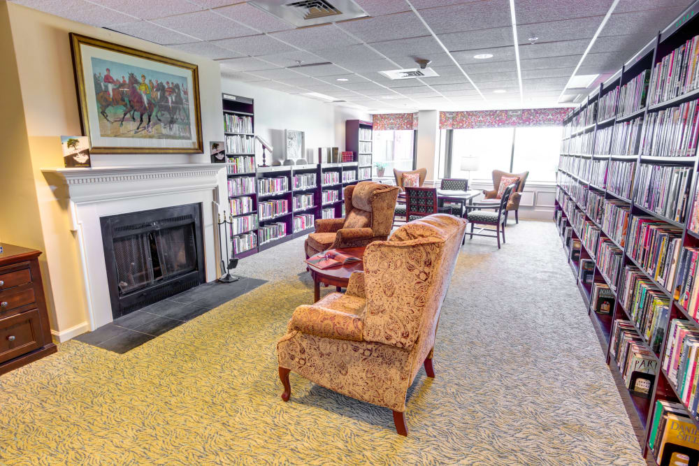 Fireplace in library with cozy chairs at Woodland Heights in Little Rock, Arkansas
