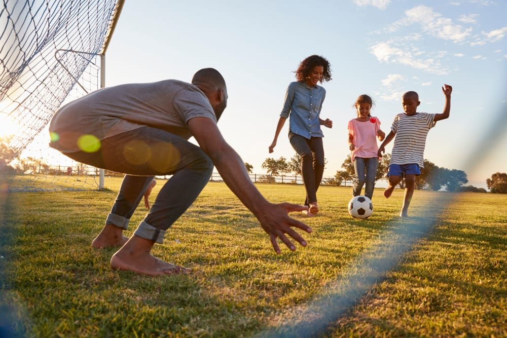 Family playing soccer together near Brookmanor in Syracuse, New York