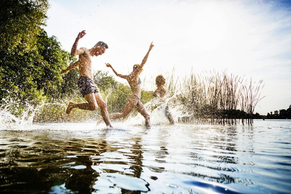 Friends jumping into a lake together near Carriage House in Syracuse, New York