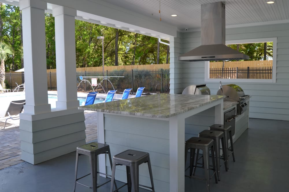 A covered outdoor grilling area by the pool at West Woods Apartments in Pensacola, Florida
