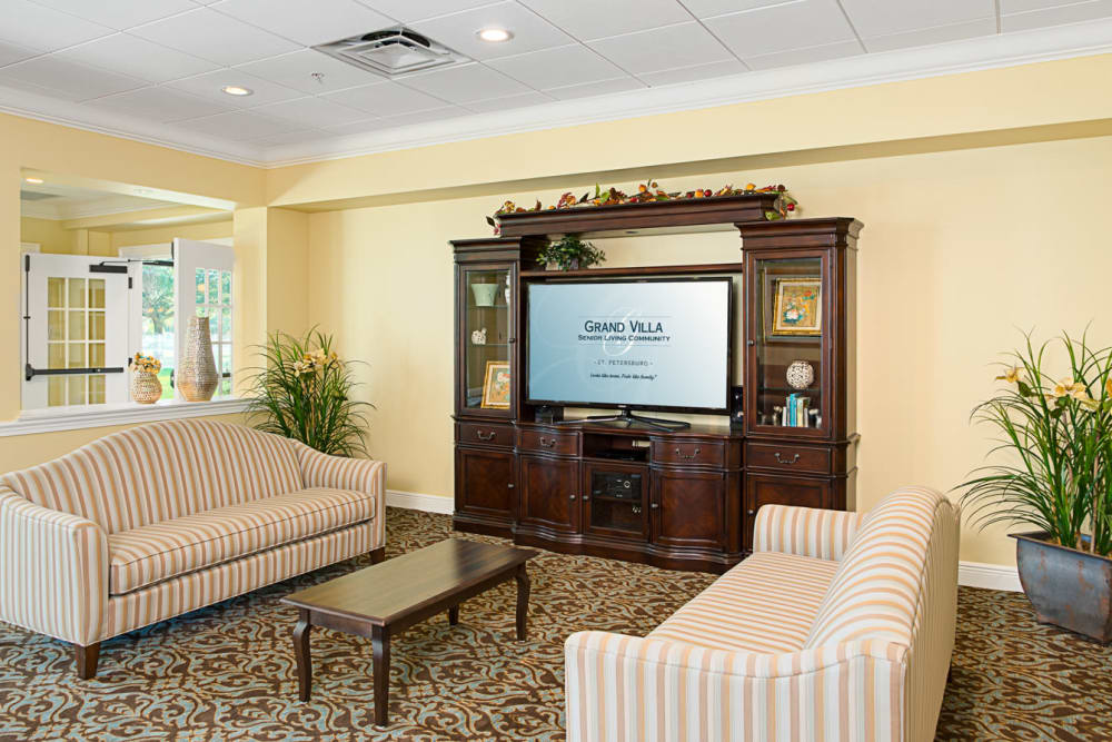 Common area with TV and couches at Grand Villa of St. Petersburg in Florida