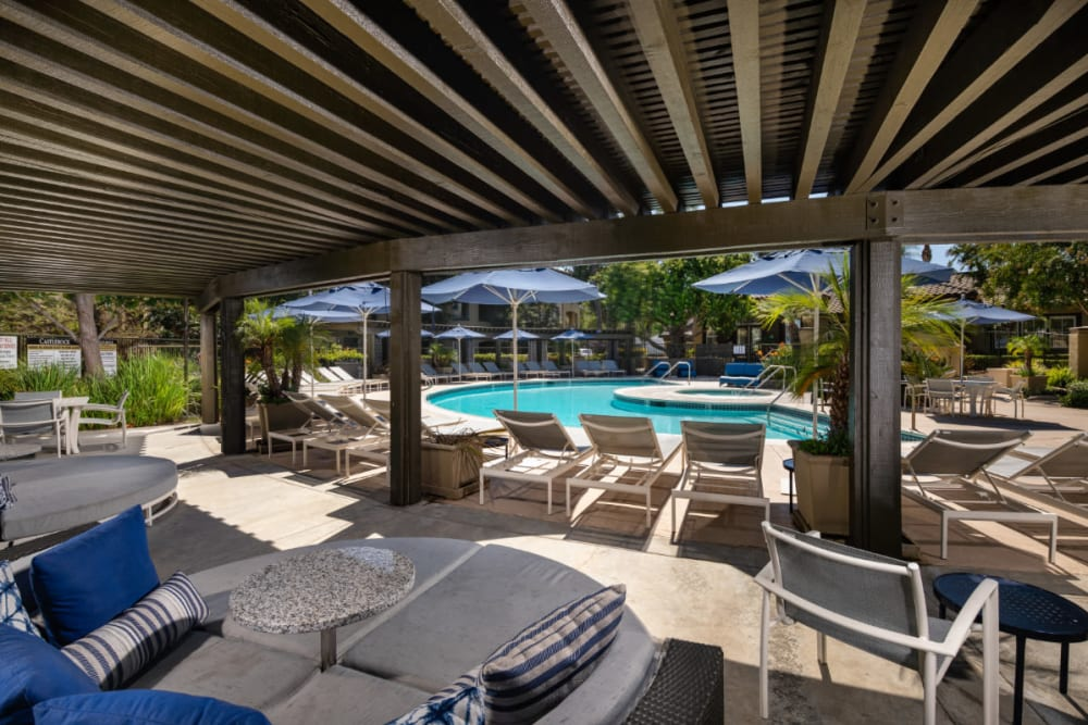 Covered outdoor seating by the hot tub and pool at Castlerock at Sycamore Highlands in Riverside, California