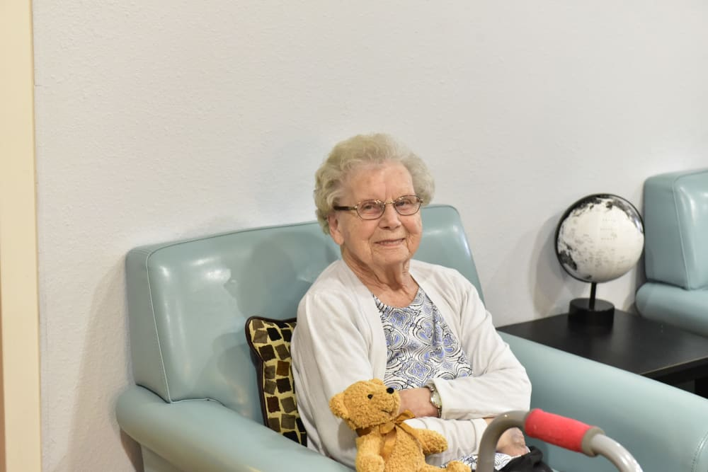 Resident relaxing and holding a stuffed animal at Reflections at Garden Place in Columbia, Illinois.