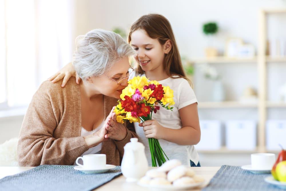 Resident smelling flowers at Garden Place Senior Living