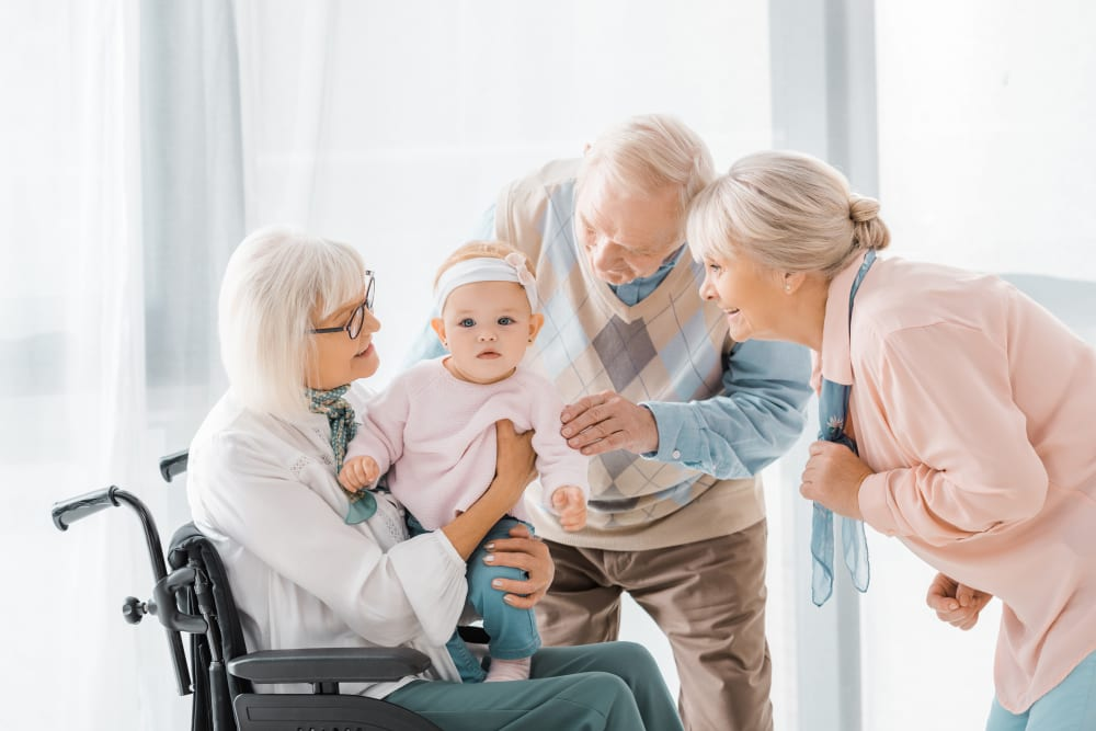 Residents playing with a new grandchild at Garden Place Senior Living