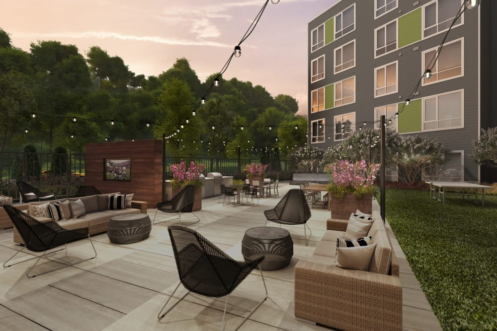 Rendering of the beautiful exterior resident courtyard with flatscreen TVs, barbecue grills, and comfortable seating at Velō in Boston, Massachusetts
