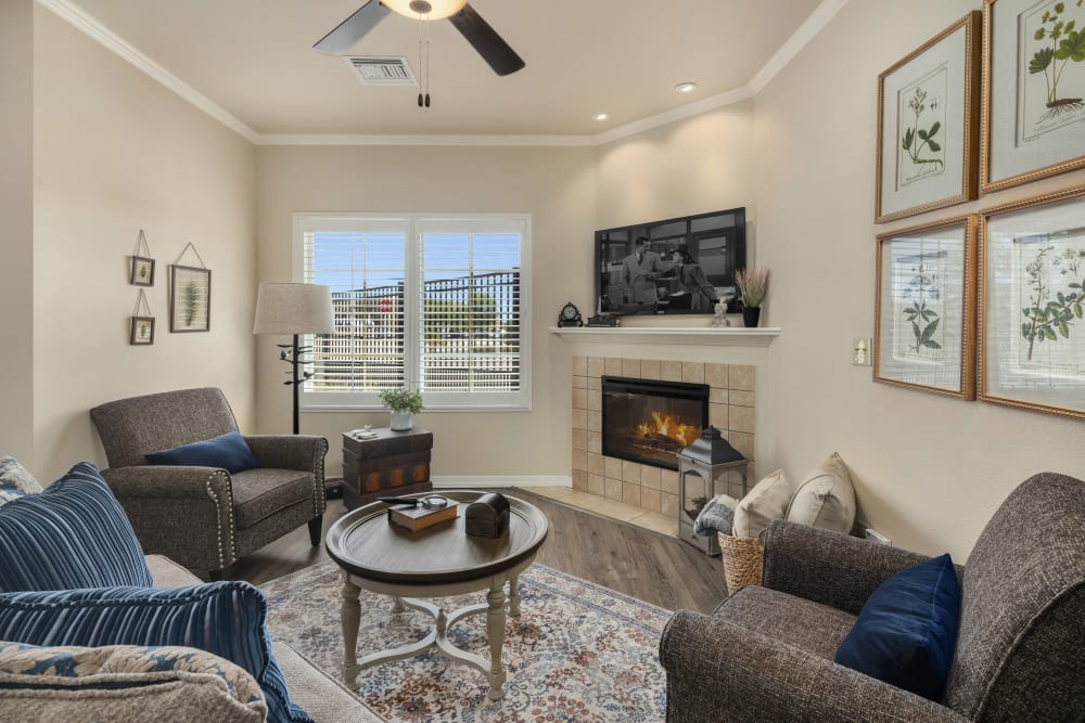 living room with fireplace and seating at The Park at Modesto Independent Living Community