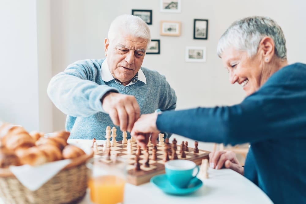 Residents of Keystone Place at Terra Bella enjoying a snack and Chess in Land O' Lakes, Florida