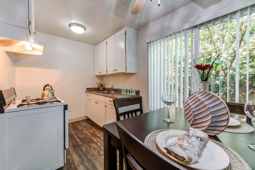 Bright kitchen and dining area with sliding door and wood style flooring at Vista Pointe I in Studio City, California