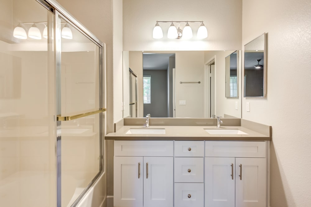 Glass shower doors and a large vanity mirror in a model home's bathroom at Sofi Westview in San Diego, California
