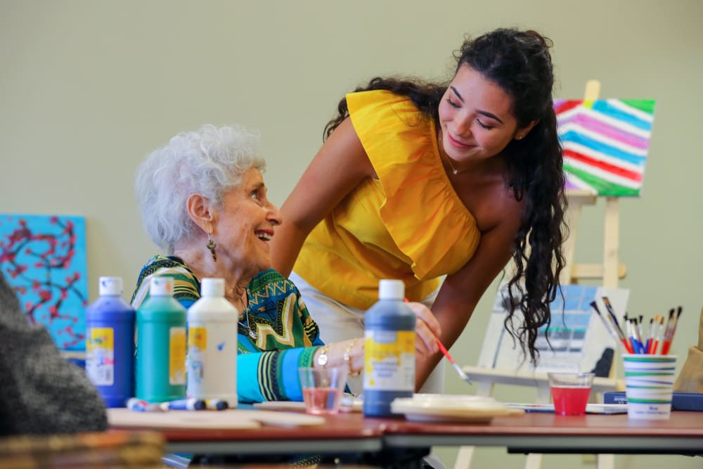 A caretaker assisting a resident with a painting activity at Harmony at Brookberry Farm in Winston-Salem, North Carolina