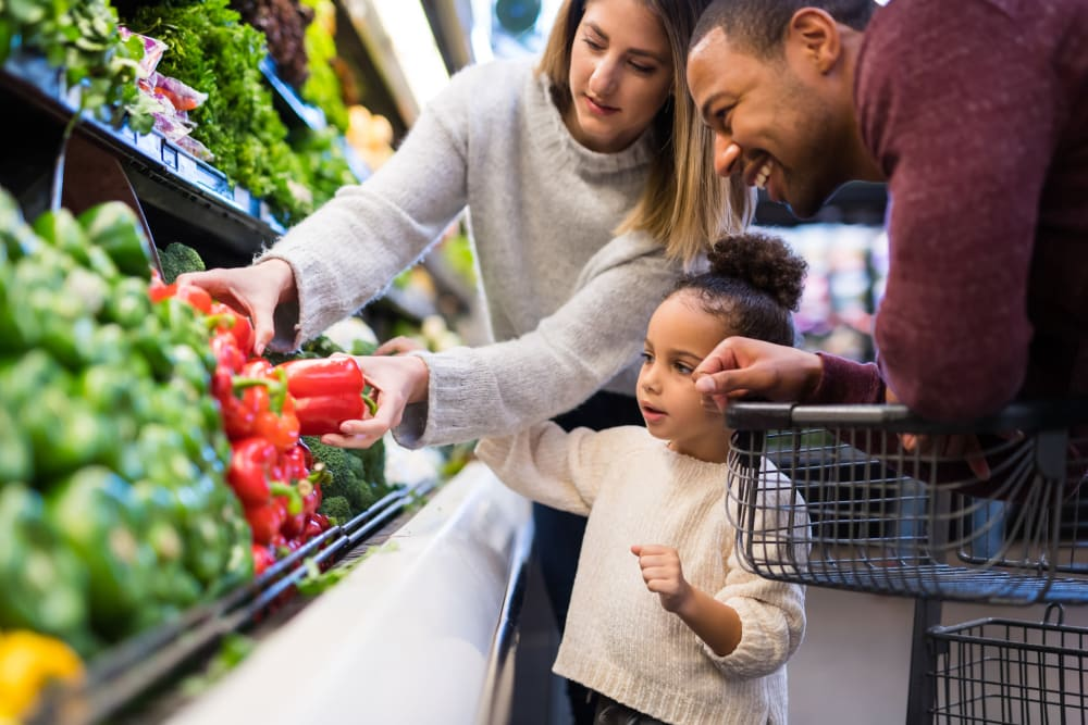 Family looking at bell peppers in a grocery store in Garland, Texas near 5th Street Crossing at City Station
