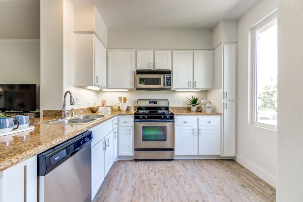 Large kitchen with a breakfast bar in a model home at Sofi Shadowridge in Vista, California