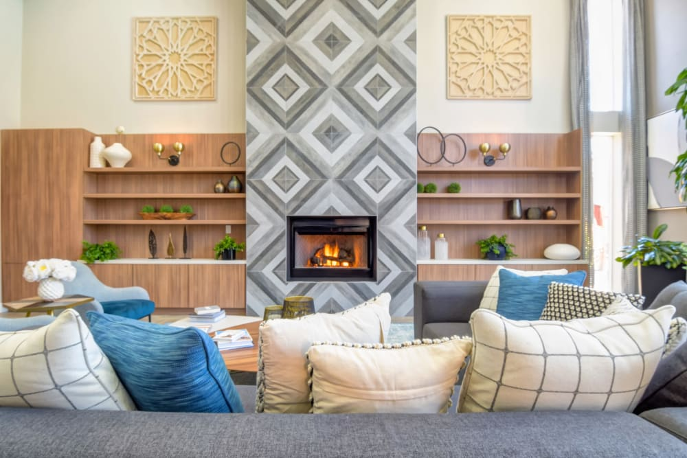 Large wrap-around couch next to a fireplace in the clubhouse at Sofi Shadowridge in Vista, California