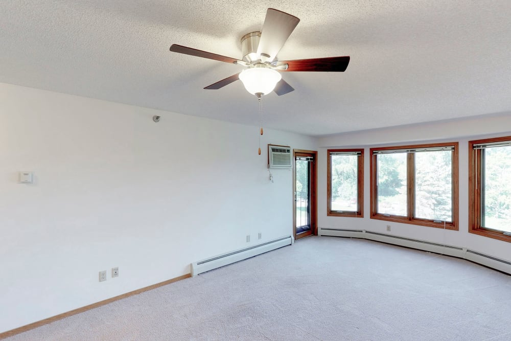 Spacious living room with a ceiling fan at Oaks Lincoln Apartments & Townhomes in Edina, Minnesota