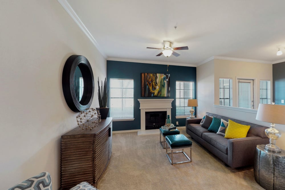 Living room with a ceiling fan at Oaks Riverchase in Coppell, Texas