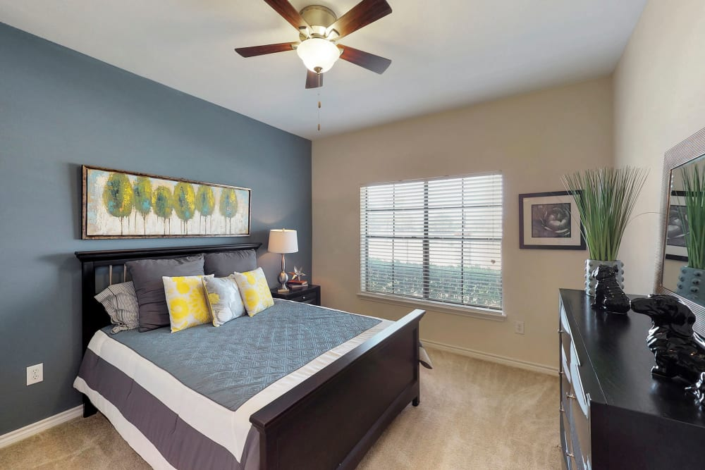 Master bedroom with a ceiling fan at Oaks Riverchase in Coppell, Texas