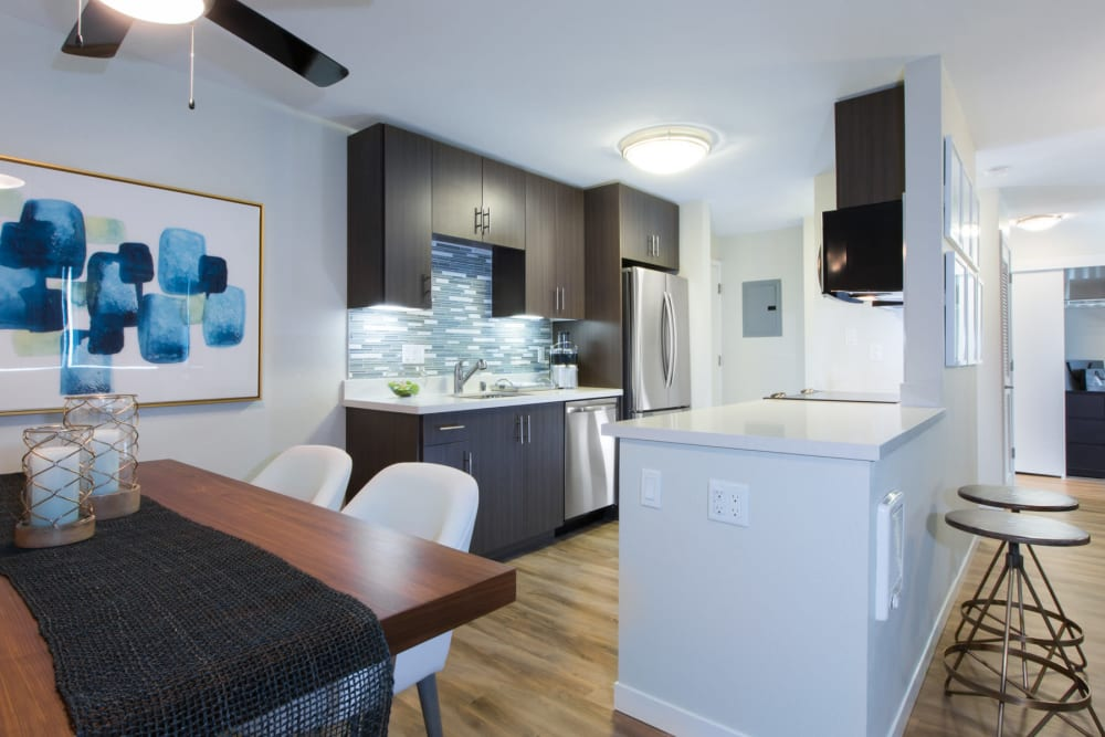 View of the modern kitchen from a model home's dining area at Sofi Belmont Glen in Belmont, California