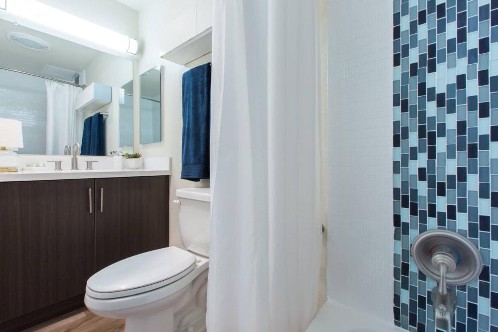 Large vanity mirror and custom tiling in a model home's bathroom at Sofi Belmont Glen in Belmont, California