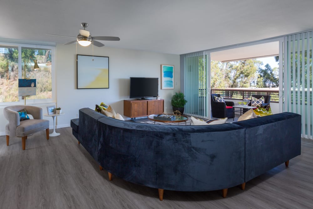 Beautiful hardwood floors and a ceiling fan in a model home's living area at Sofi Belmont Glen in Belmont, California