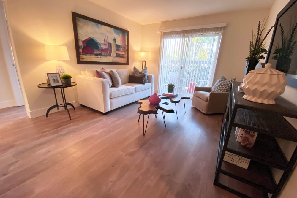 Living room with wood-style flooring at Cypress Pointe Apartments in Gilroy, California
